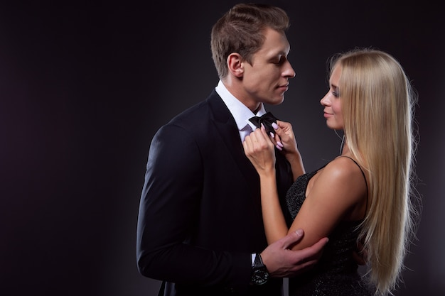 A charming blonde woman in a black evening dress lovingly ties a tie for her man