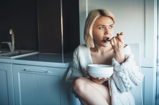 どこかを見ながら床のキッチンでシリアルを食べる魅力的なブロンドの女性