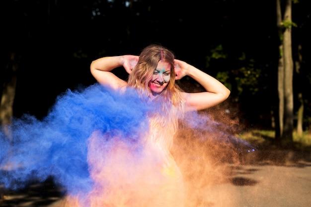 乾燥したホーリーペイントの爆発を楽しんでいる魅力的なブロンドの女性
