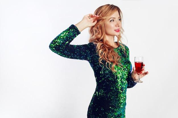 スタジオで白い背景の上のワインのガラスでポーズをとって驚くほど輝くスパンコールドレスの魅力的なブロンドの女性。