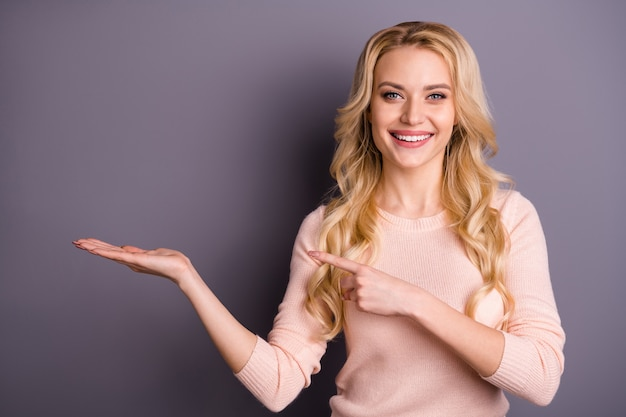 Очаровательная блондинка в розовом свитере позирует у фиолетовой стены
