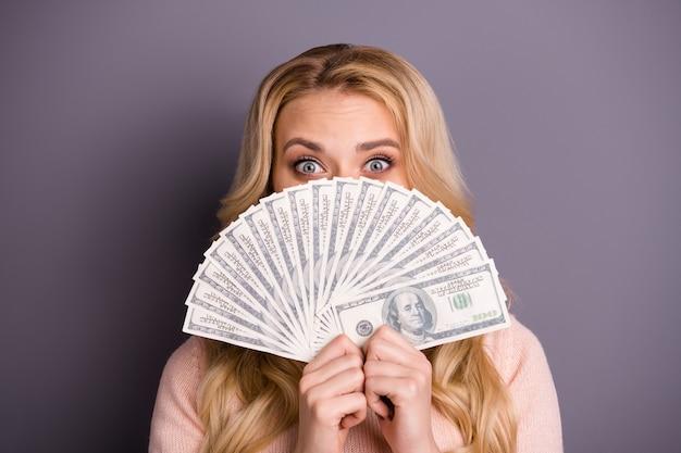 Очаровательная блондинка в розовом свитере позирует с деньгами у фиолетовой стены