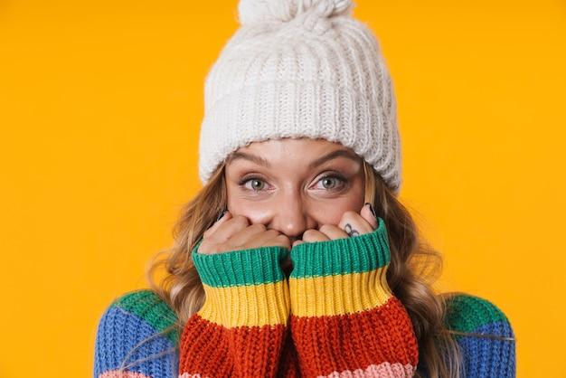 Очаровательная блондинка в зимней шапке согревает в своем свитере, изолированном над желтой стеной