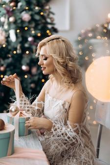 매력적인 금발의 여자는 크리스마스 트리 앞에 앉아 선물 상자를 엽니 다