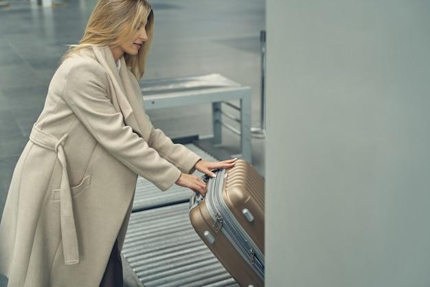 セミポジションで立って、チェックをする前に彼女の荷物を見て魅力的なブロンドの女性