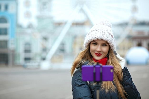 ニット帽をかぶって、冬の路上で自分撮りをしている魅力的な金髪の女性観光客。テキスト用のスペース