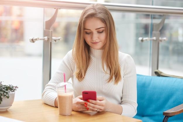 매력적인 금발의 여자는 스마트 폰을 사용, 카페에서 소파에 앉아, 소셜 네트워크를 서핑, 친구에게 문자 메시지를 보냅니다. 사랑스러운 소녀는 레스토랑 창 위에 격리 포즈.