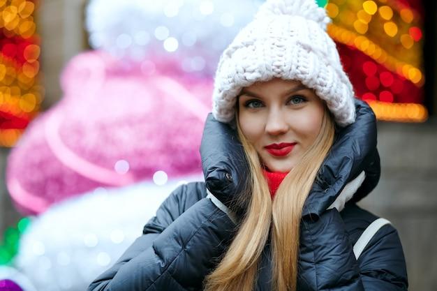 ボケ味と花輪の背景の上の通りでポーズをとってニット帽を身に着けている魅力的なブロンドの女性