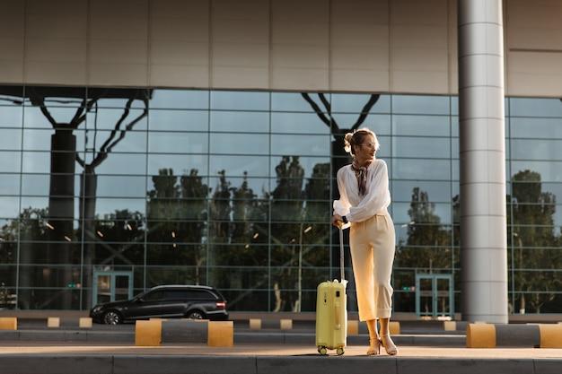 Affascinante donna bionda in camicetta bianca, pantaloni beige e occhiali da vista si muove vicino all'aeroporto