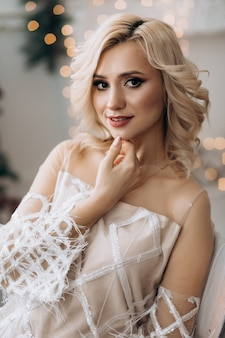 Charming blonde woman in white dress poses in a room with large christmas tree