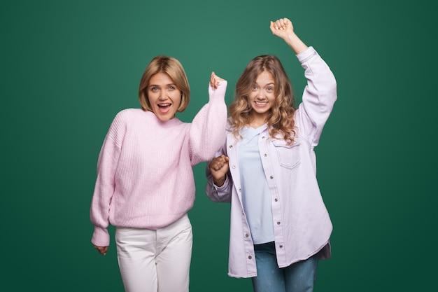 上の手と笑顔で緑の壁にポーズをとって魅力的な金髪の女性