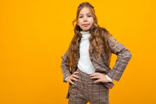 古典的な茶色のジャケットの魅力的な金髪少女ポーズオンオレンジコピースペース