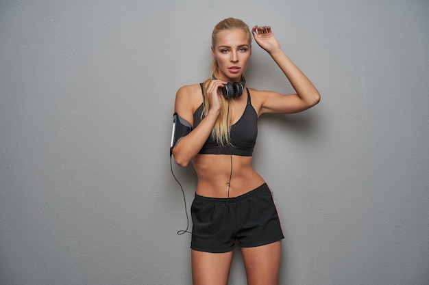 Charming blue-eyed young slim blonde woman with ponytail hairstyle wearing headphones on her neck, looking to camera with serious face, posing over light grey background in athletic wear