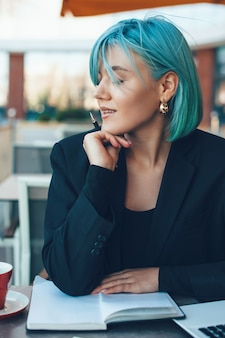 노트북에 몇 가지 아이디어를 쓰는 동안 커피 숍에서 포즈 매력적인 파란 머리 여자