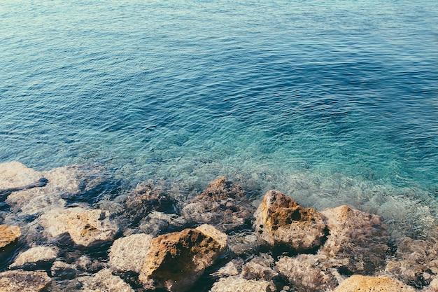 Очаровательная голубая прозрачная вода эгейского моря в греции с большими камнями на берегу. загипнотизировать голубую воду.