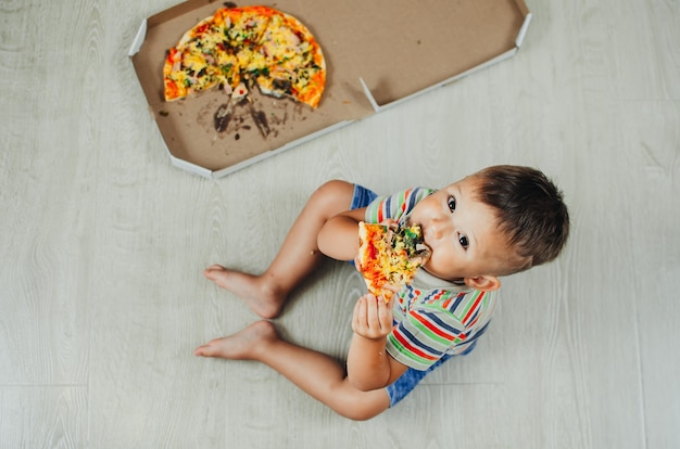 Charming boy sitting on the floor eating pizza top view