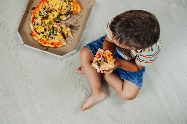 피자 탑 뷰를 먹고 바닥에 앉아 매력적인 소년