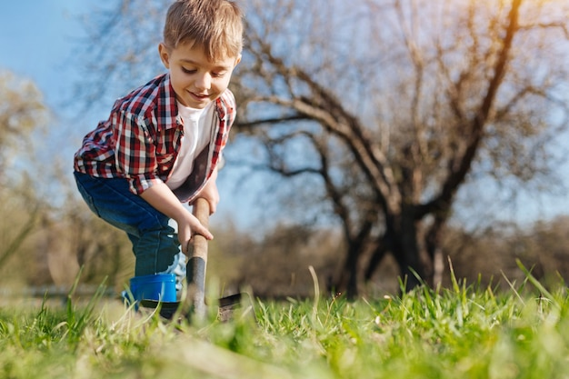 A charming boy wearing plaid shirt digging a hole in the ground to plant a tree in backyard