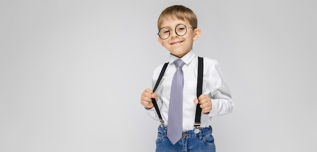 A charming boy in a white shirt, suspenders, a tie and light jeans stands. the boy in glasses pulled the suspenders