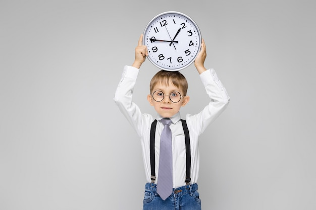A charming boy in a white shirt, suspenders, a tie and light jeans stands on a gray . a boy holds a watch on his head
