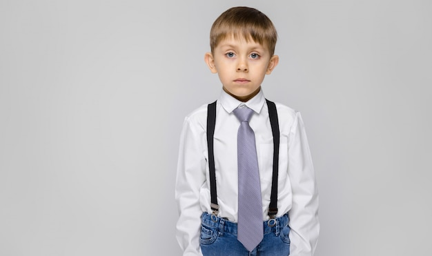 A charming boy in a white shirt, suspenders, a tie and light jeans stands on a gray