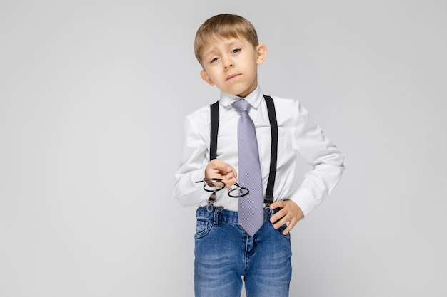 A charming boy in a white shirt, suspenders, a tie and light jeans stands