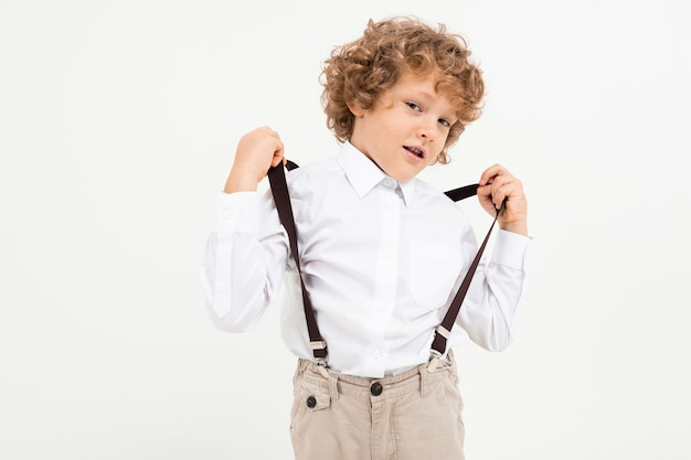 Charming boy with curly hair in white shirt with black suspenders stands isolated on white