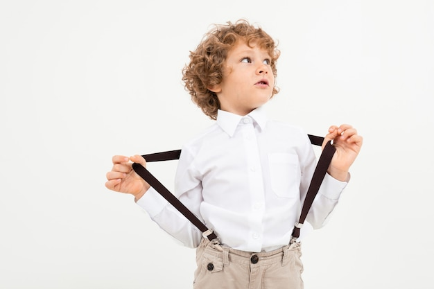 Charming boy with curly hair in white shirt with black suspenders stands on white