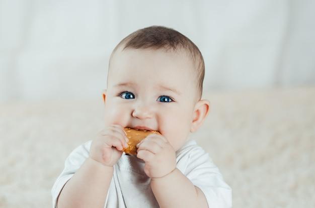 Очаровательная грудь ребенка сидит и облизывает печенье, почесывая зубы