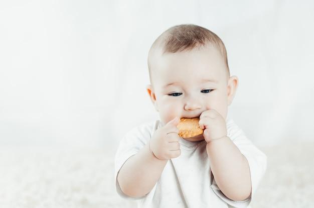 魅力的な胸の子供が座ってビスケットを舐め、歯を掻く