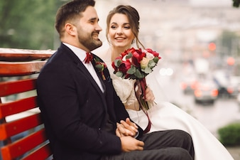 Charming bride and groom hold each other tender sitting on the bench outside