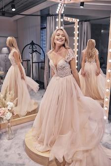 매력적인 신부. 웨딩 드레스를 입고 신부 가게의 거울 앞에 서서 웃고 있는 매력적인 젊은 여성의 전체 길이