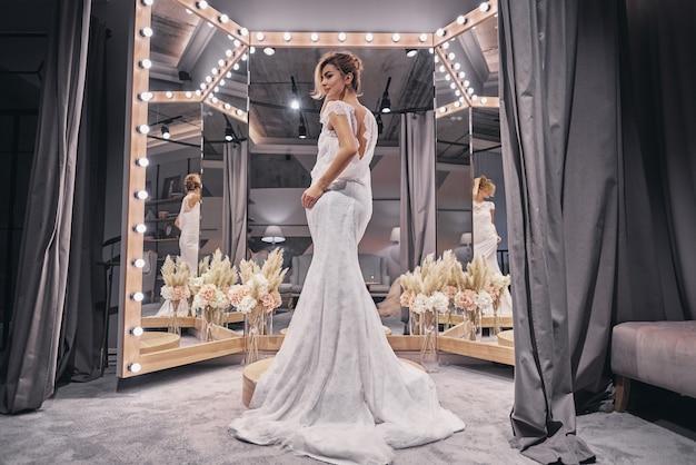 매력적인 신부. 신부 가게에서 거울 앞에 서 있는 동안 놀라운 웨딩 드레스를 입고 매력적인 젊은 여성의 전체 길이