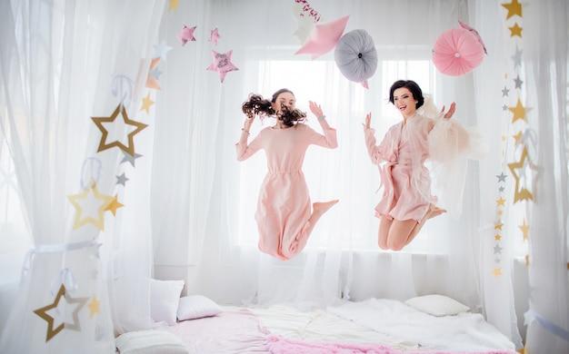 Очаровательная невеста в розовом шелковом платье и подружка невесты в платье персика прыгают на кровать