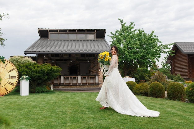 The charming bride keeps a wedding bouquet and walking along yard