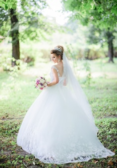 Charming bride poses with colorful wedding bouquet in the park