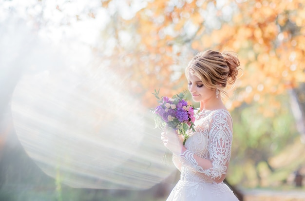 Charming bride poses with violet wedding bouquet on the green lawn