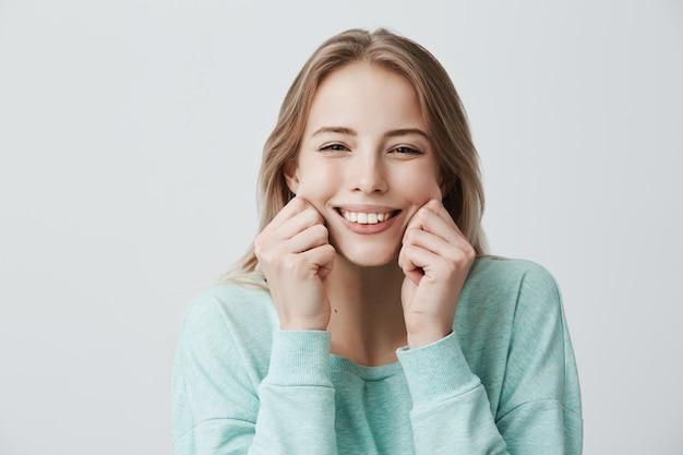 明るい青のセーターを着ているブロンドの長い髪を持つ金髪の若いヨーロッパ人女性の完璧な歯で広く笑顔で魅力的な頬をつまんで、あざけって、良い気分で楽しんでいます。顔の表情と感情