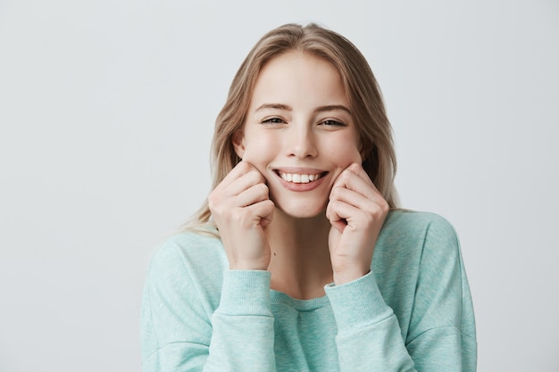 Charming broadly smiling with perfect teeth young european woman with blonde long hair wearing light blue sweater, pinching cheeks, mocking, having good mood and fun. face expressions and emotions