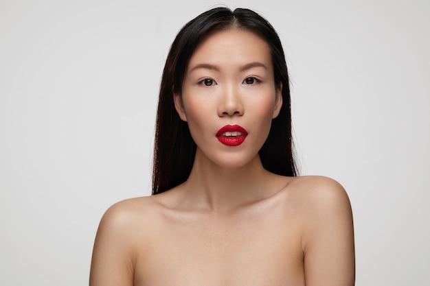 彼女の白い完璧な歯を示し、白い壁の上に立って、落ち着いて見える赤い唇を持つ魅力的な茶色の目のかなり若いブルネットの女性