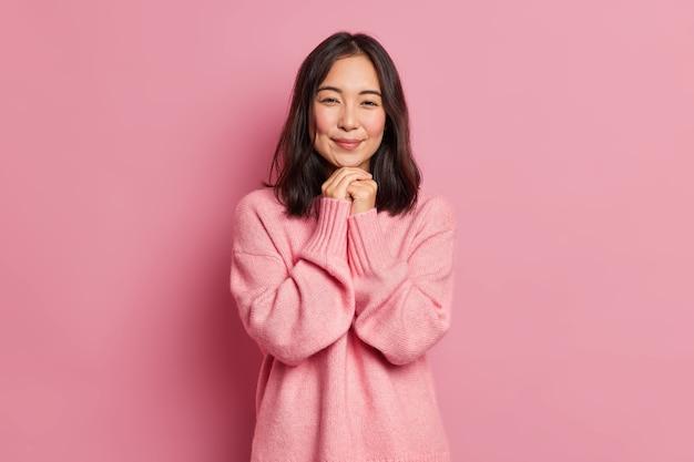 Affascinante ragazza asiatica bruna con espressione tenera ha le guance arrossate tiene le mani sotto il mento vestite in pose di ponticello sciolto