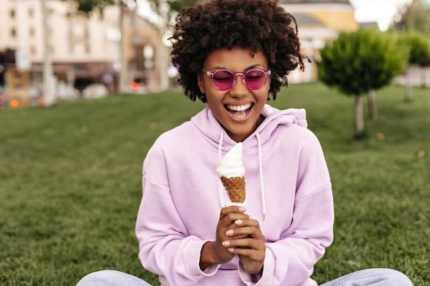 Очаровательная брюнетка кудрявая молодая женщина в розовой толстовке с капюшоном, стильных ярких солнцезащитных очках поет, держит мороженое и сидит на траве на улице