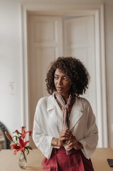 Charming brunette dark-skinned woman in burgundy pants and white blouse touches silk scarf, looks away and leans on wooden table in cozy room