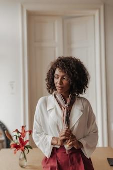 버건디 바지와 흰색 블라우스를 입은 매력적인 갈색 피부의 여성이 실크 스카프를 만지고, 시선을 돌리고 아늑한 방에 있는 나무 테이블에 기대어 있습니다.