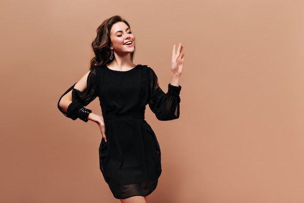 Charming brunette girl in black dress is smiling and waving hand in greeting on beige background.