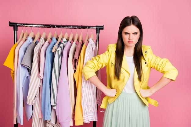 Очаровательная брюнетка девушка выбирает стильную одежду в шоу-руме гардероба