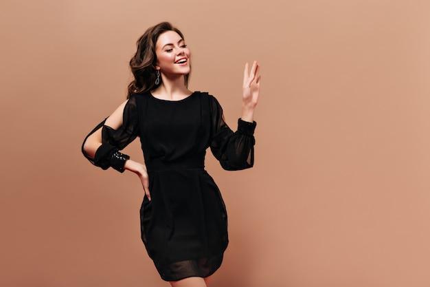 黒のドレスを着た魅力的なブルネットの少女は、ベージュの背景に挨拶で笑顔と手を振っています。