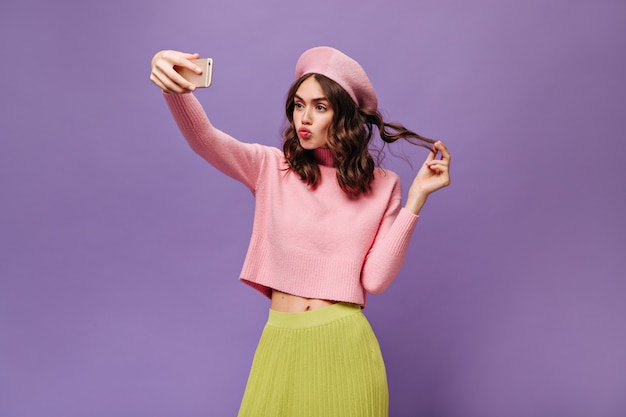 魅力的なブルネットの女の子が髪に触れ、スマートフォンを持って、自分撮りをします