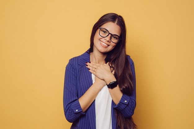 Charming brunette in glasses with long hair dressed in dark blue suit cute smiling, folded hands on her chest, looks grateful, over yellow background with copy space. people sincere emotions.