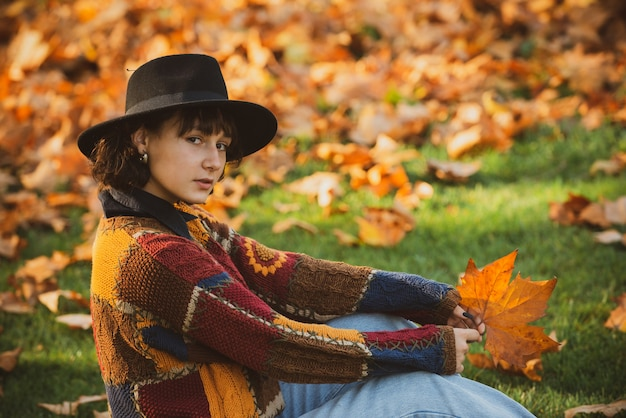Charming brunette in hat with autumnal leaves. autumn queen wearing cozy sweater. autumnal forest in golden and yellow colors. hipster woman in vintage hat walking in park.